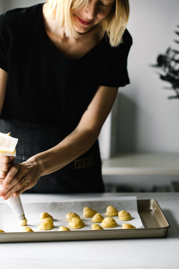 Shot of woman piping choux paste onto a baking sheet