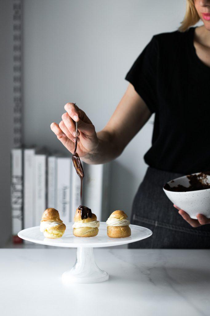 Shot of woman drizzling chocolate ganache onto 3 Choux à la Crème