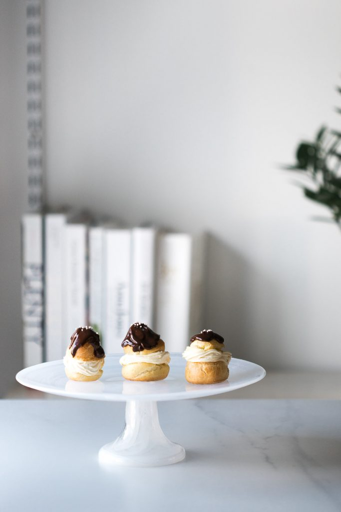 Shot of 3 Choux à la Crème sitting on a cake stand