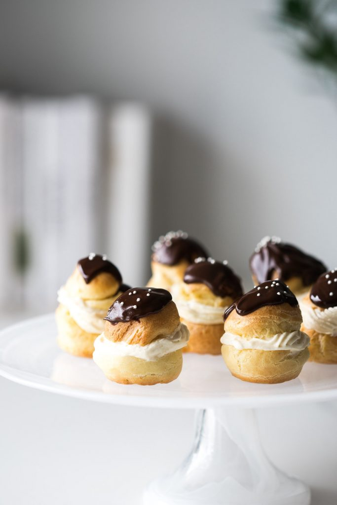 Several finished Choux à la Crème sitting on a cake stand