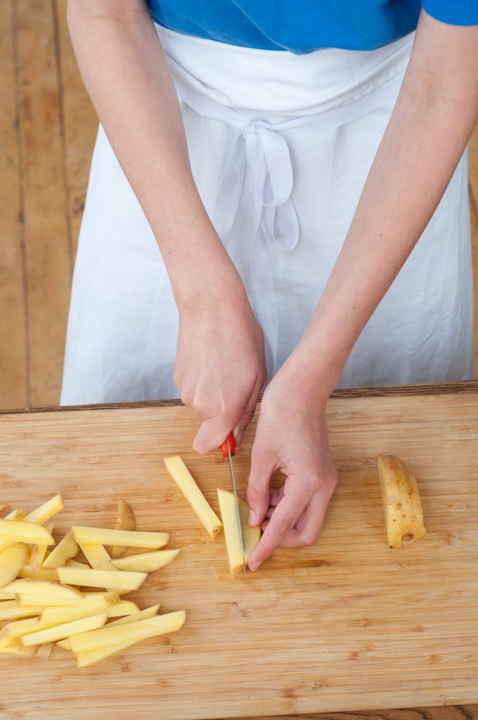 Kids chopping potatoes for oven baked fries from In the French kitchen with kids by Mardi Michels