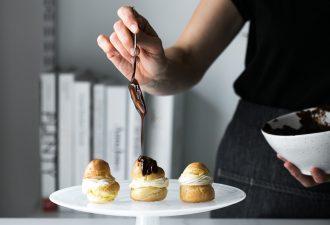 Shot of woman drizzling chocolate ganache onto Choux à la Crème