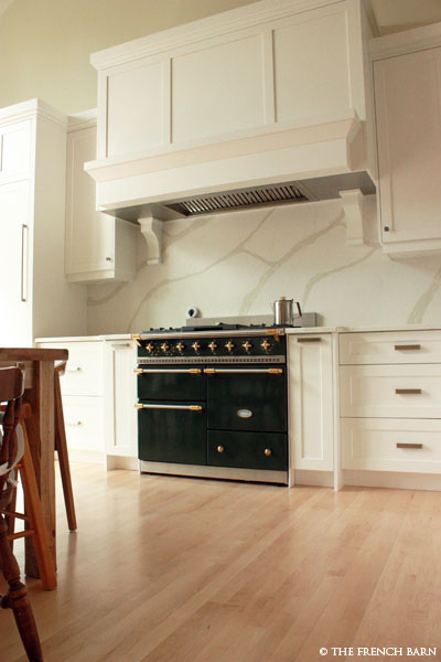 Green stove with cream cabinetry